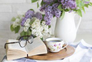 Kuvassa kahvikuppi, kirja ja kukkamaljakko luovat kodinomaisen tunnelman.