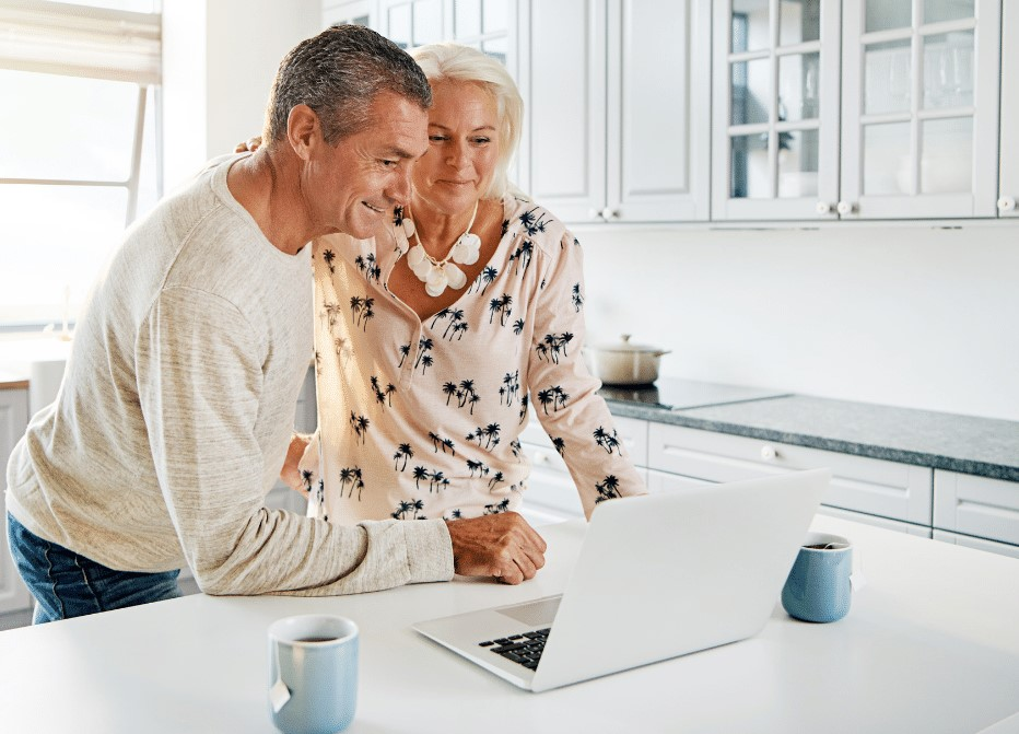 vanhempi pariskunta seisoo keittiössä ja katselee kannettavalta tietokoneelta sisältöä