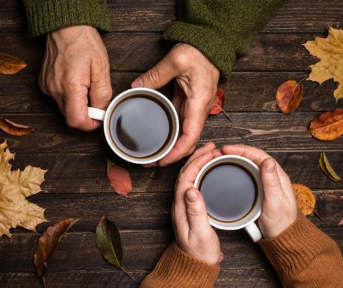 Kahdet kädet pitelevät kahvikuppeja.