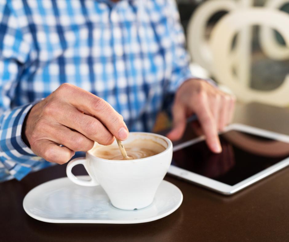 Mies käyttää tablettitietokonetta ja hämmentää kahvia.