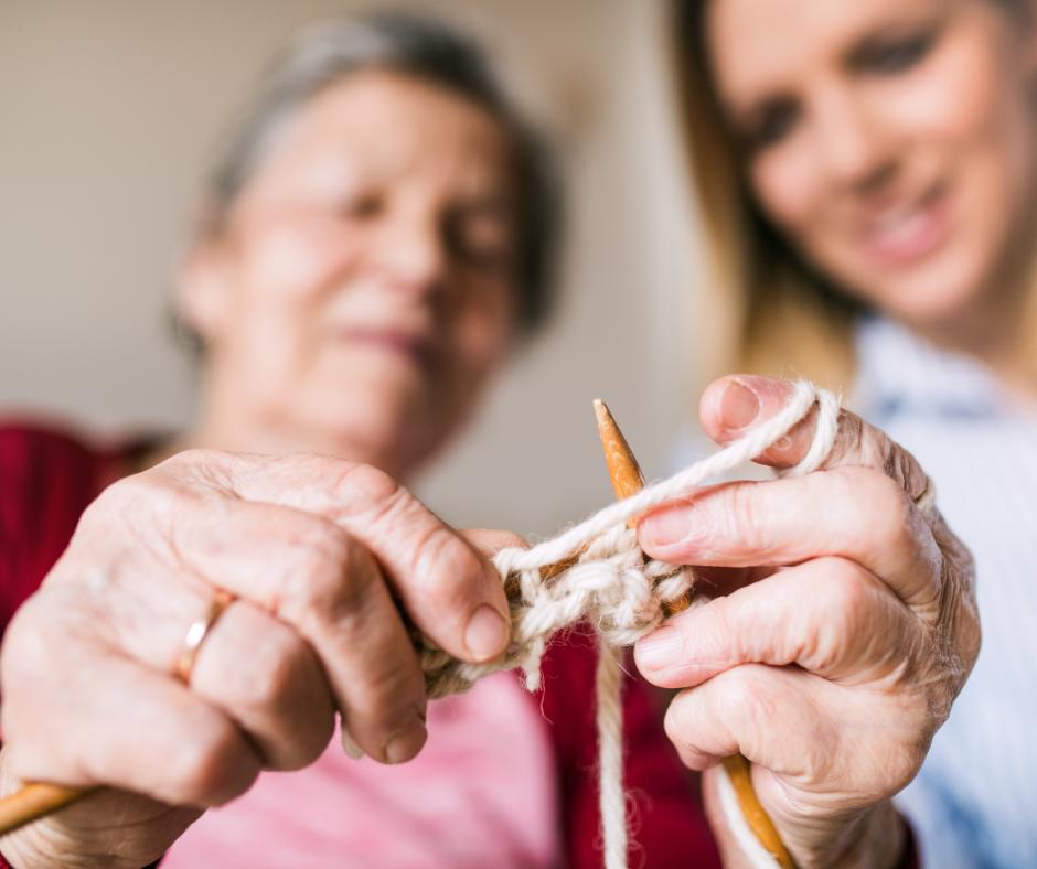 Vanhempi nainen neuloo. Nuorempi nainen katselee sivusta ja hymyilee.