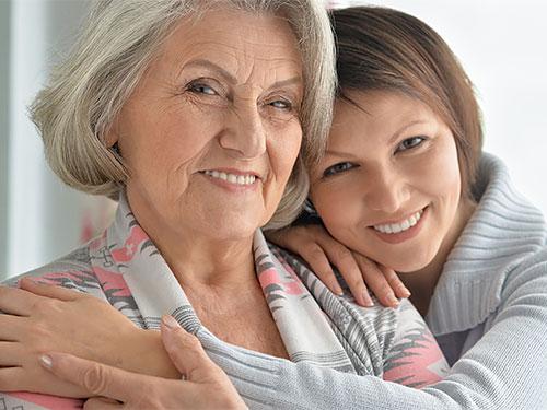 Vanhempi nainen, jonka olkaan nojaa nuori nainen.