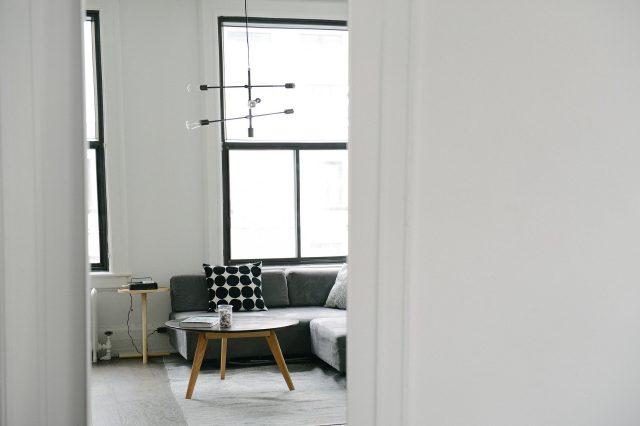 Valoisa ja tilava koti, oviaukosta näkyy sohva ja pöytä.