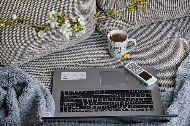 Sohvalla tietokone, puhelin, teekuppi ja kukkia.