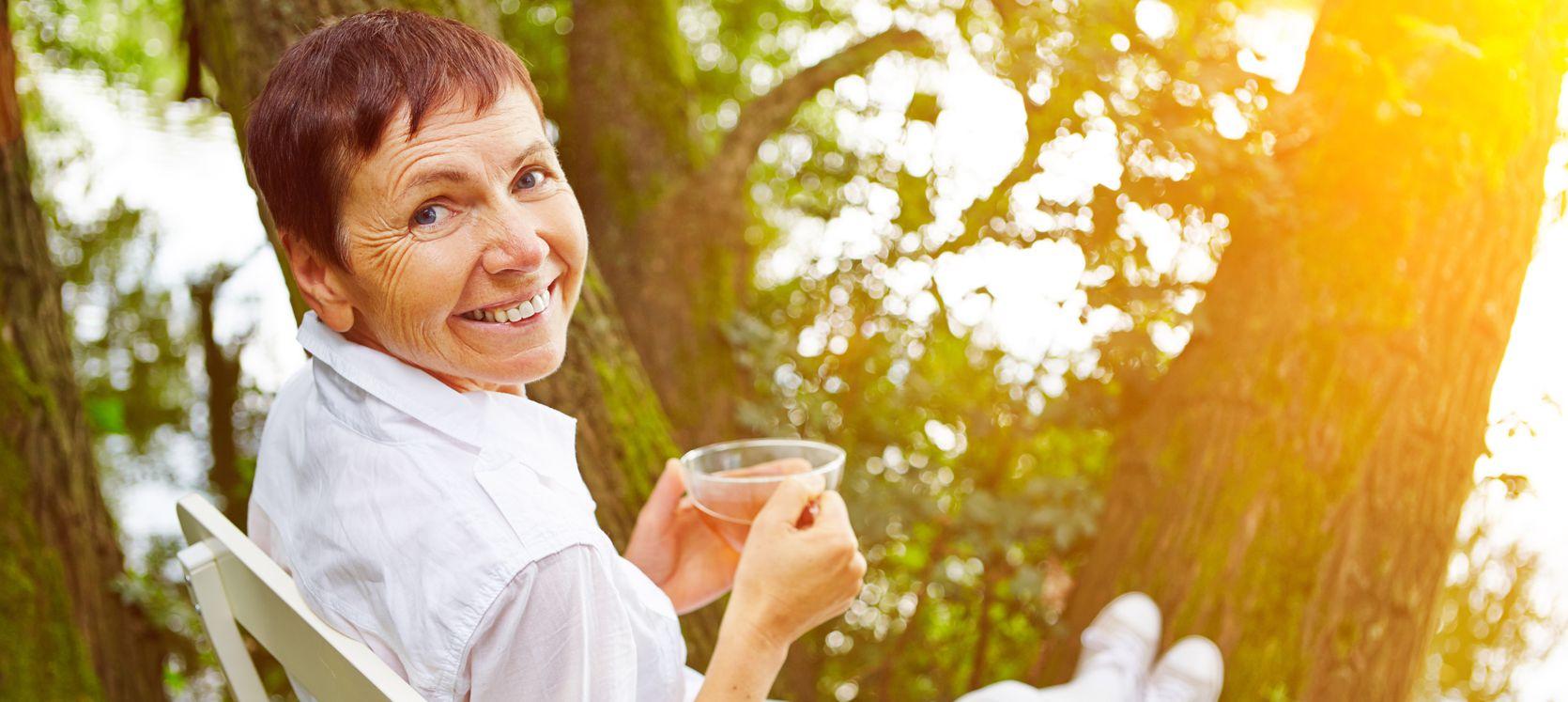 Ikääntynyt nainen istuu ulkona puuston lomassa teekuppi kädessä ja hymyilee olkansa yli