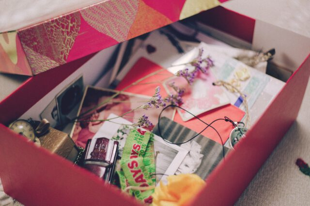 Vanhoja kuvia ja muistoesineitä punaruutuisessa pahvilaatikossa.
