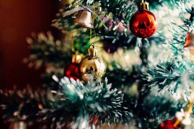 Palloja ja kimaltavia koristenauhoja joulukuusen oksassa.