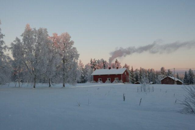 Punainen vanhahko omakotitalo lumisen maalaismaiseman keskellä.